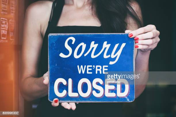 Barista holding up Closed sign in a coffee shop