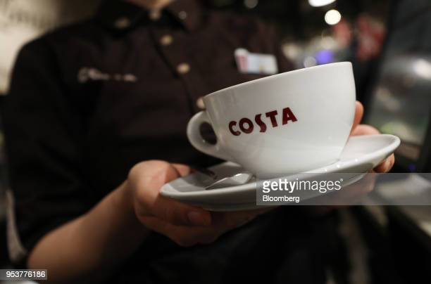 A barista holds a cup and saucer of coffee in a Costa Coffee shop operated by Whitbread Plc in London UK on Wednesday May 2 2018 Whitbread is betting...