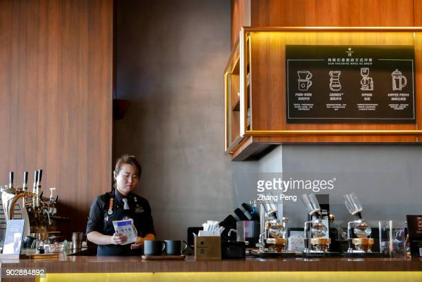 A barista is making coffee for customers in a Starbucks reserve coffee shop Since January 1st Starbucks took back the management rights of more than...