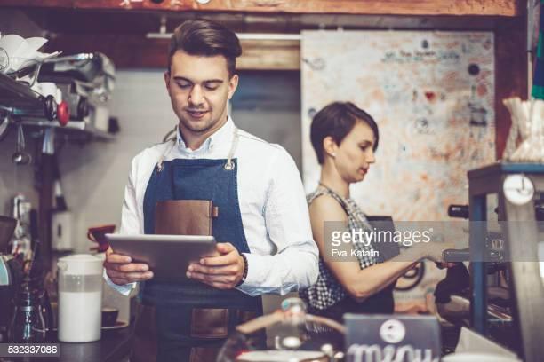 Barista está usando una tableta digital en una cafetería