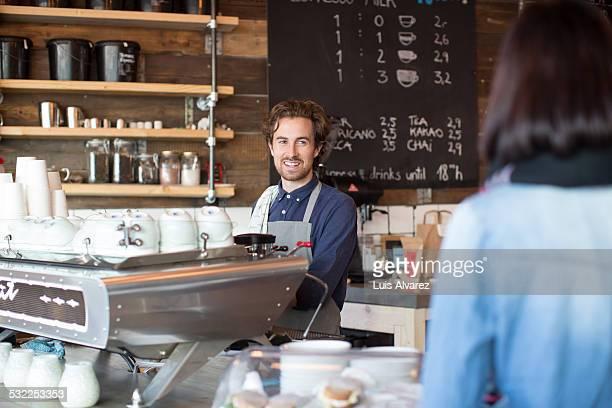 Barista looking at female customer at counter