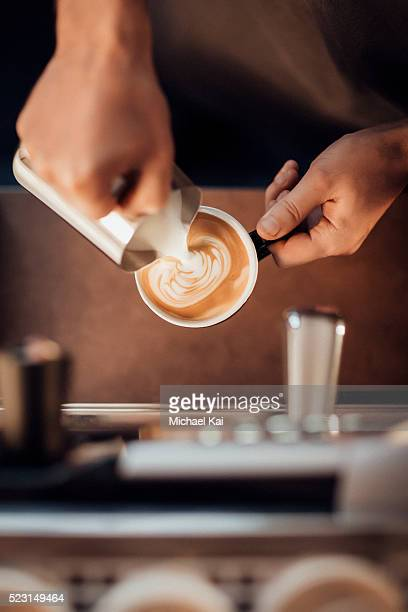 Barista making a latte milk coffee with milk froth
