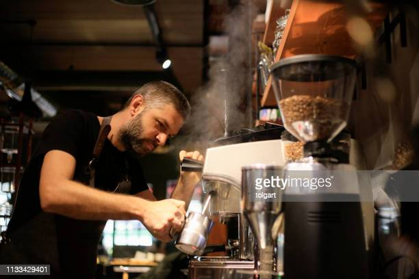 barista making coffee for customers at cafe - small stock pictures, royalty-free photos & images
