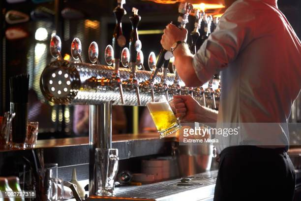 barista pouring beer into glass - brewers stock pictures, royalty-free photos & images