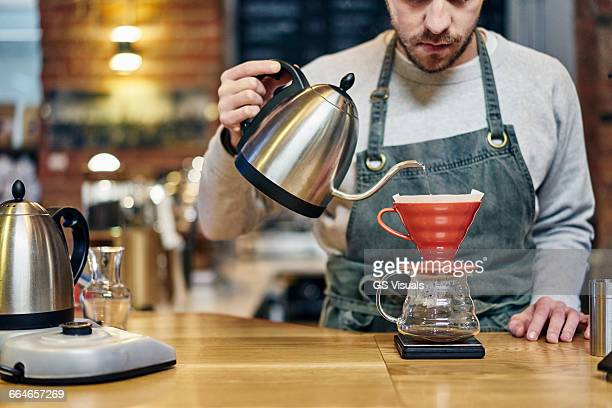 Barista pouring boiling water into coffee filter at coffee shop