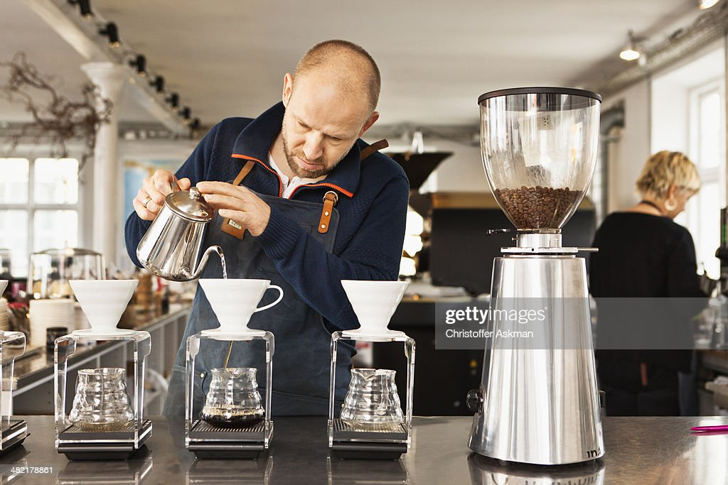Barista pouring boiling water into coffee filters : Stock Photo