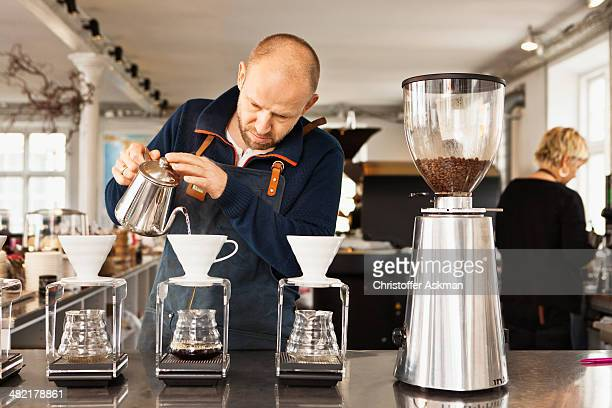 Barista pouring boiling water into coffee filters