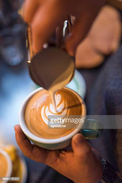 barista pouring milk for latte art - espresso stock photos and pictures