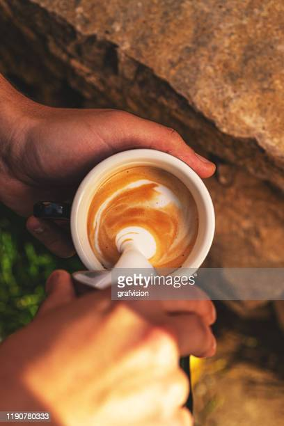barista pouring milk coffee cup for