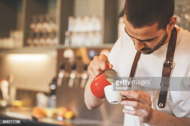 Barista pouring milk in coffee
