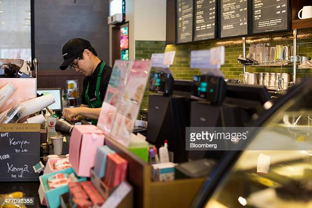 A barista pours milk into a cup as he prepares a coffee at a Starbucks Coffee Korea Co store in Gimpo South Korea on Friday March 7 2014 Starbucks...