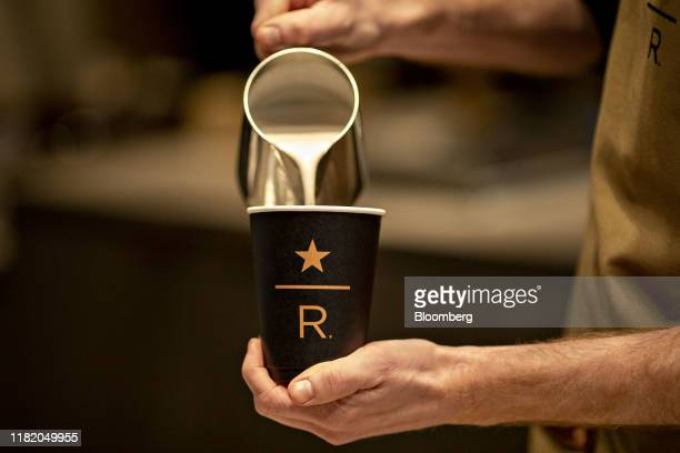 A barista pours milk into a cup while preparing a cappuccino during a preview of the new Starbucks Reserve Roastery in Chicago Illinois US on Tuesday...