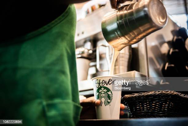 A barista pours steamed milk into a beverage cup marked 'Steven' inside a Starbucks Corp cafe in the Sandton area of Johannesburg South Africa on...
