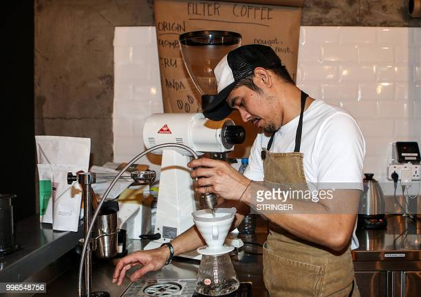 A barista prepares an order at the 'Flat White' cafe in the Qatari capital Doha's Tawar Mall on June 8 2018 Tawar Mall looks like any of Qatar's...