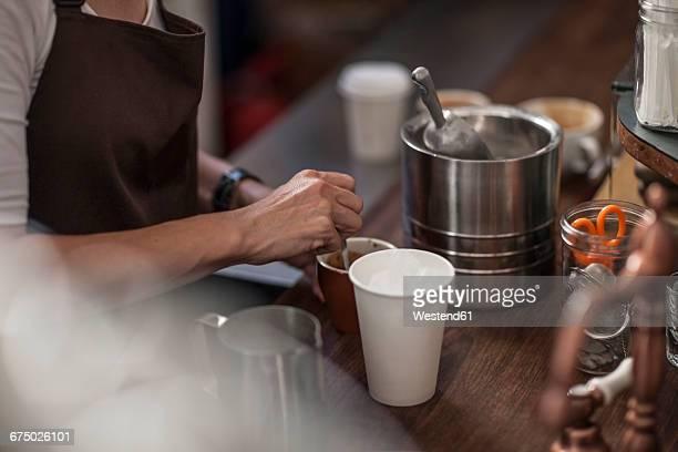 Barista preparing coffee behind counter