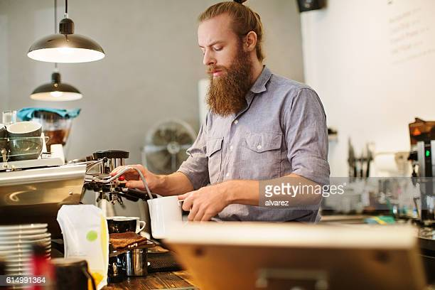 Barista preparing cup of coffee at restaurant
