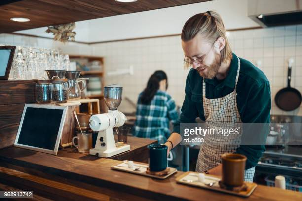 a barista preparing to serve coffee in a cafe - artisan stock photos and pictures