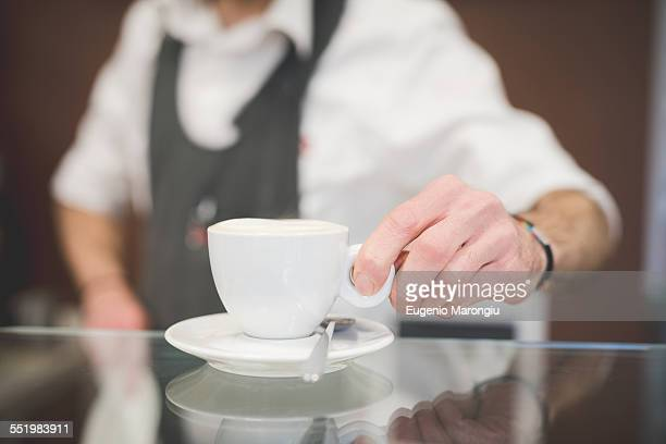 Barista serving coffee over the counter