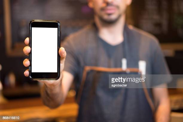barista showing smartphone screen - showing stock photos and pictures