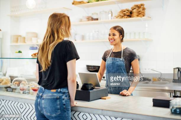 barista smiles at a female customer in a cafe - cash register stock pictures, royalty-free photos & images