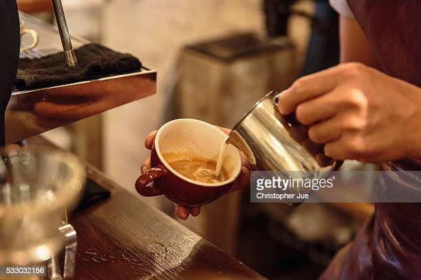 Barista Takaya Hashimoto prepares a cafe latte at a local specialty coffee shop on May 20 2016 in Tokyo Japan With the rise of specialty coffee shops...