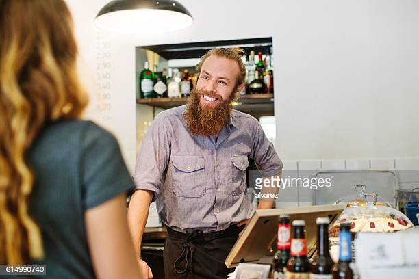 Barista talking to female customer