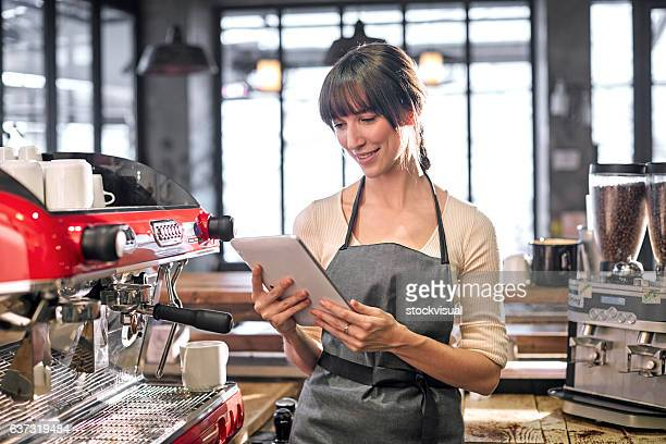 Barista using tablet in cafe.