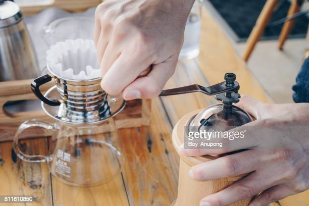 Barista using the coffee grinder to grinding the roasted coffee beans.