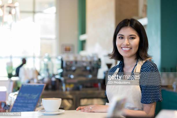 barista waits for customer to pick up coffee order - minority groups stock pictures, royalty-free photos & images