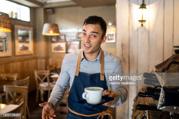 barista welcoming customers to have a drink coffee - coffee drink stock pictures, royalty-free photos & images