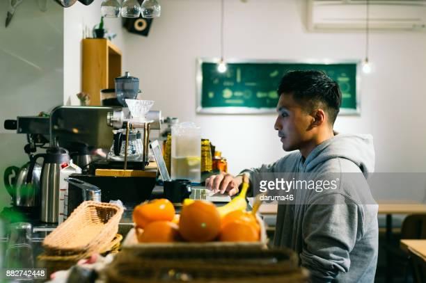 バリスタ カフェ カウンターで注文を管理するためのラップトップに取り組んで