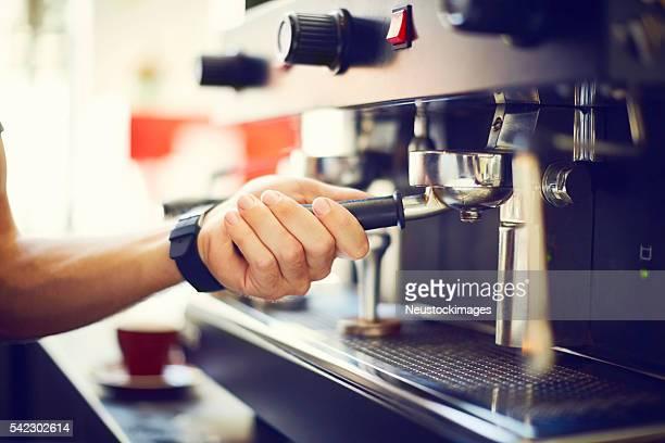 Barista's hand adjusting portafilter