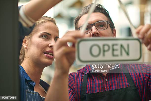 Baristas hanging up open sign together