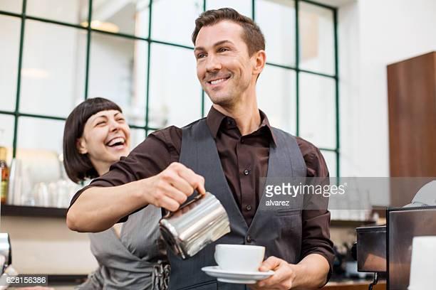 Baristas preparing coffee at cafe counter