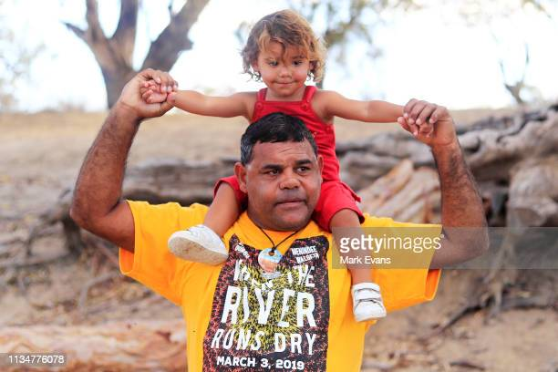 Barkandji man and independent candidate for the seat of Barwon Owen Whyman looks on with his child Kaakuru on the dry bed of the Darling Barka river...