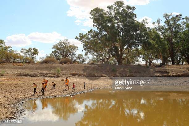 Barkandji man and independent candidate for the seat of Barwon, Owen Whyman and his family walk on the dry bed of the Darling -Barka river on March...