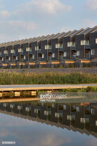 Barking Riverside Housing Development Barking United Kingdom Architect Sheppard Robson 2014 Landscaped creek and pond area with housing terrace beyond