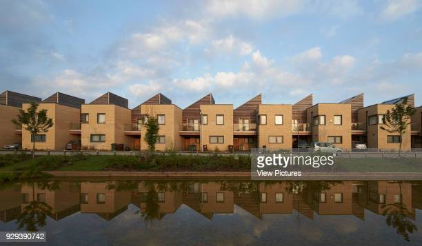Barking Riverside Housing Development Barking United Kingdom Architect Sheppard Robson 2014 Front elevation of terrace with reflection in creek