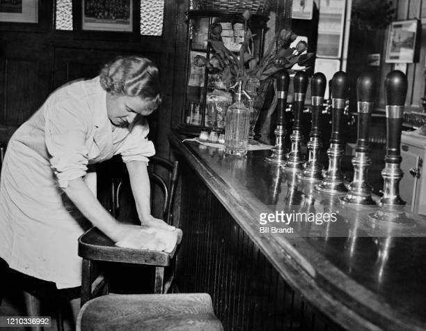Barmaid Alice cleaning a bar stool at the start of her working day at The Crooked Billet pub in Tower Hill London 1939 Original Publication Picture...