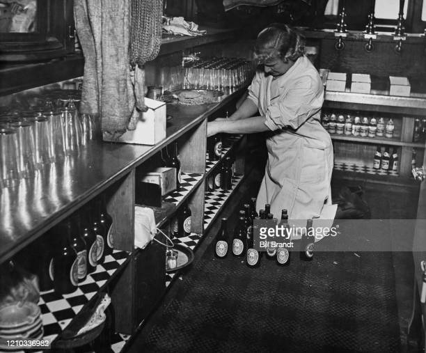Barmaid, Alice, sorting and dusting beer bottles at the start of her working day at The Crooked Billet pub in Tower Hill, London, 1939. Original...