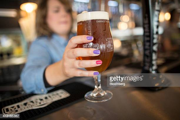 A barmaid hands a glass of London Pale Ale to a customer in the tasting rooms at the Meantime Brewing Co brewery in London UK on Friday May 15 2015...