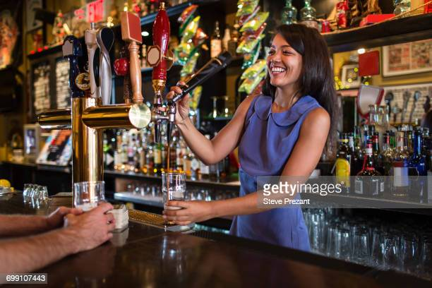 Barmaid serving beer from pump in public house