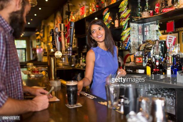 Barmaid serving male customer in public house