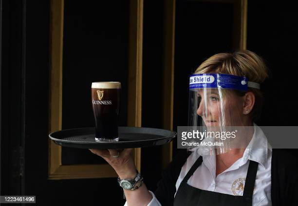 Barmaid waits for a pint of Guinness to settle before serving a customer at Murrays pub on Grafton street on June 29, 2020 in Dublin, Ireland....