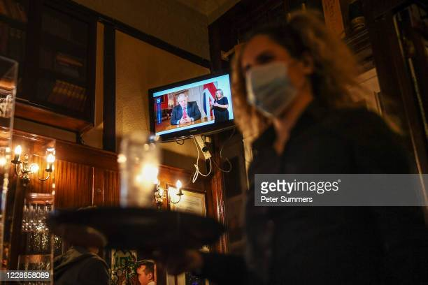 Barmaid walks past as British Prime Minister Boris Johnson makes a televised address to the nation inside the Westminster Arms pub on September 22,...