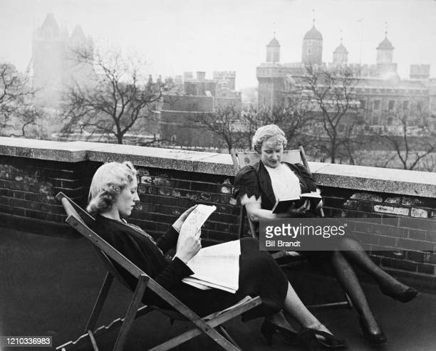 Barmaids Ivy and Alice reading in deckchairs during their rest hour on the roof of The Crooked Billet pub in Tower Hill London 1939 In the background...
