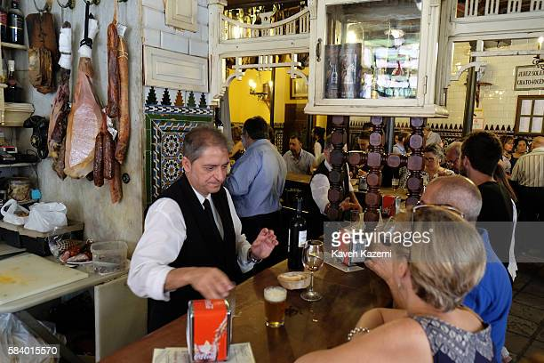 A barman attends to people at lunch time in El Rinconcillo a very famous and classic Tapas Bar on June 25 2016 in Seville Spain