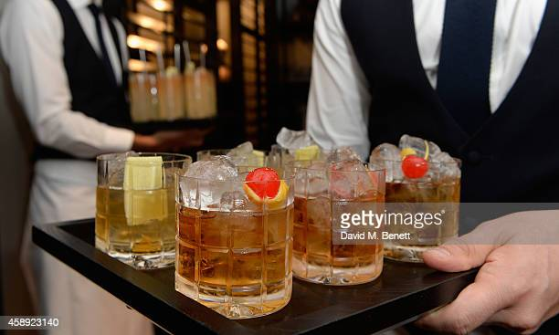 Barman carries glasses of Haig Club whisky during the opening of the new Thom Sweeney RTW & MTM Store on November 13, 2014 in London, England.