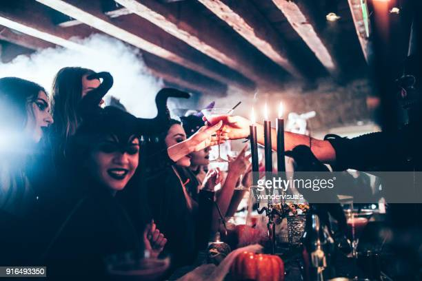barman giving cocktail to woman at halloween party - halloween party stock photos and pictures