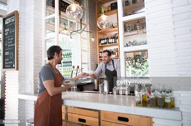 Barman handling order to waiter at a restaurant